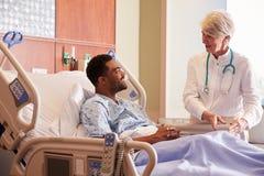 Paciente femenino del doctor Talking To Male en cama de hospital imagen de archivo libre de regalías