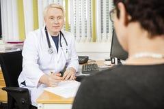 Paciente femenino masculino del doctor Writing Prescription For en el escritorio fotos de archivo
