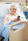 Paciente femenino mayor en cama de hospital usando el teléfono móvil Imágenes de archivo libres de regalías