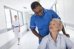 Paciente femenino mayor en silla de ruedas y enfermera en hospital Imagenes de archivo