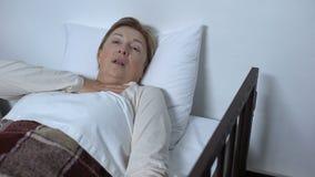 Paciente femenino mayor enfermo que miente en lecho de enfermo, apenas respirando y pidiendo ayuda almacen de video