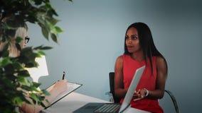 Paciente femenino negro que comparte problemas con el psicólogo de sexo femenino metrajes