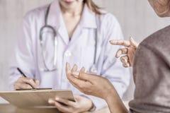 Paciente femenino que habla y que explica sobre problema de salud al doctor imagen de archivo