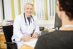Paciente femenino sonriente del doctor Writing Prescription For en el escritorio imagen de archivo