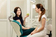 Paciente hermoso de la mujer que tiene tratamiento dental en la oficina del ` s del dentista La mujer sonriente sostiene una manz foto de archivo