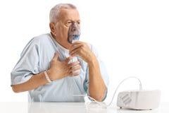 Paciente idoso que tem a dor no peito e que usa um inalador fotografia de stock royalty free