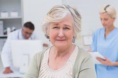 Paciente infeliz con el doctor y la enfermera que trabajan en fondo Imágenes de archivo libres de regalías