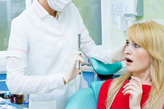 Paciente joven en la oficina del dentista, asustada de la inyección anestésica, imágenes de archivo libres de regalías