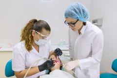 Paciente joven en silla dental Concepto de la medicina, de la odontología y de la atención sanitaria foto de archivo libre de regalías