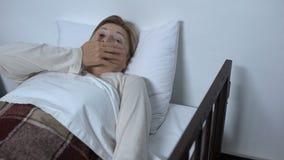 Paciente jubilado de la mujer que miente en ataque de asma de sensación del lecho de enfermo y que pide ayuda almacen de metraje de vídeo