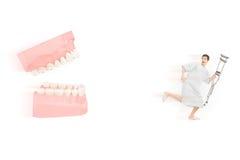 Paciente masculino asustado con la muleta que corre lejos de las dentaduras abiertas Fotos de archivo