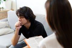 Paciente masculino de la tensión joven que se sienta en el sofá que consulta con el psicólogo de sexo femenino fotografía de archivo