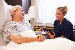 Paciente masculino de Talking To Senior da enfermeira na cama de hospital foto de stock