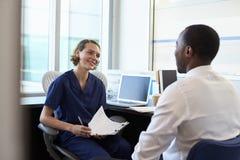 Paciente masculino del doctor In Consultation With en oficina Fotos de archivo libres de regalías