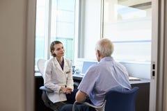 Paciente masculino del doctor In Consultation With en oficina Foto de archivo libre de regalías