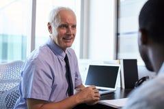Paciente masculino del doctor In Consultation With en oficina Fotografía de archivo