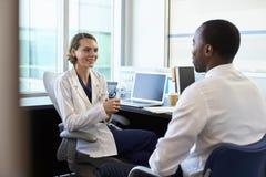 Paciente masculino del doctor In Consultation With en oficina Imagen de archivo libre de regalías
