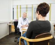 Paciente masculino del doctor Writing Prescription For en el escritorio fotos de archivo libres de regalías