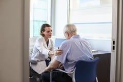 Paciente masculino deprimido del doctor In Consultation With Imagenes de archivo