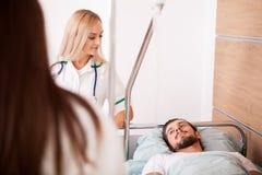 Paciente masculino enfermo en sitio de hospital al lado de enfermeras fotografía de archivo libre de regalías