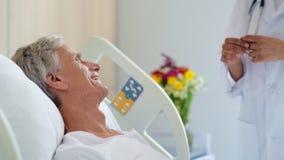 Paciente masculino envelhecido alegre que fala com seu doutor profissional video estoque