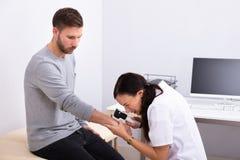 Paciente masculino femenino del doctor Examining Skin Of fotos de archivo