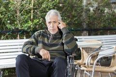 Paciente masculino mayor pensativo que se sienta en silla de ruedas en el césped foto de archivo libre de regalías