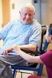 Paciente masculino mayor que es empujado hacia adentro silla de ruedas por la enfermera Imágenes de archivo libres de regalías