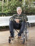 Paciente masculino mayor que se sienta en silla de ruedas en el césped imagen de archivo libre de regalías