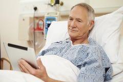 Paciente masculino mayor que usa la tableta de Digitaces en cama de hospital foto de archivo
