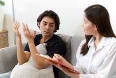 Paciente masculino novo que senta-se no problema de consulta do sofá com psicólogo fêmea fotos de stock royalty free