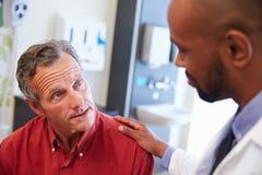 Paciente masculino que es tranquilizado por el doctor In Hospital Room Imagen de archivo libre de regalías