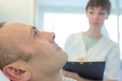 Paciente masculino que está sendo tranquilizado pela enfermeira In Hospital Room fotografia de stock royalty free