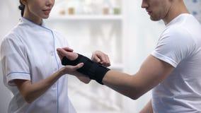 Paciente masculino satisfeito profissional do apoio de pulso da fixação do ortopedista, cuidados médicos video estoque