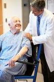 Paciente masculino superior que está sendo empurrado a cadeira de rodas pelo doutor Fotografia de Stock