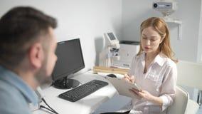 Paciente masculino tendo a consulta com doutor de olho video estoque