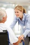 Paciente mayor con el doctor de sexo femenino joven imagen de archivo