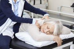 Paciente mayor de Giving Massage To del fisioterapeuta en centro de rehabilitación Foto de archivo libre de regalías