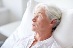 Paciente mayor de la mujer que miente en cama en la sala de hospital Imagen de archivo