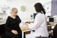 Paciente mayor del doctor Explaining Model To que sufre de Shoulde fotos de archivo libres de regalías