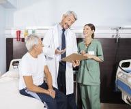 Paciente mayor feliz del doctor Explaining Report To en centro de rehabilitación imagenes de archivo