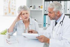 Paciente mayor femenino que visita a un doctor Foto de archivo libre de regalías