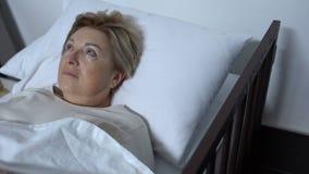 Paciente mayor preocupante que miente en lecho de enfermo y que mira alrededor, enfermedad de los alzheimers almacen de metraje de vídeo