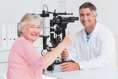 Paciente mayor que gesticula los pulgares para arriba mientras que se sienta con el óptico Imagenes de archivo