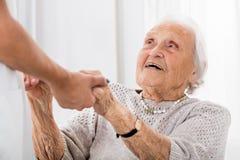 Paciente mayor que lleva a cabo las manos del doctor de sexo femenino imágenes de archivo libres de regalías