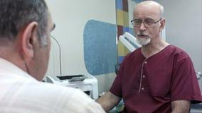 Paciente mayor teniendo consulta con el doctor en hospital almacen de metraje de vídeo