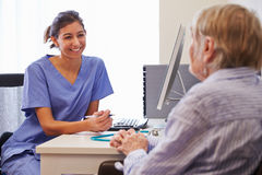 Paciente mayor teniendo consulta con la enfermera In Office Foto de archivo