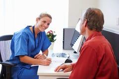 Paciente mayor teniendo consulta con la enfermera In Office Fotos de archivo libres de regalías
