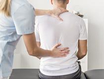 Paciente na fisioterapia que faz exercícios físicos com seu terapeuta fotografia de stock