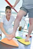 Paciente que aprende andar com fisioterapeuta fêmea foto de stock royalty free